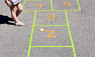 girl playing hopscotch made of colorful tape